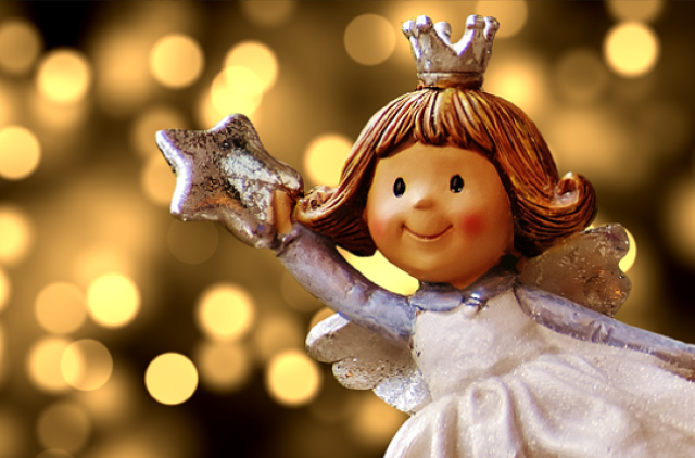 A Christmas angel decoration with cosy yellow lights in the background.
