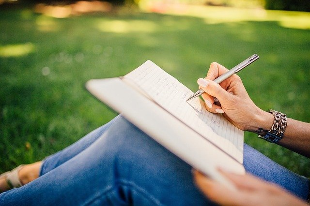 Woman writing her journal while sitting on the grass