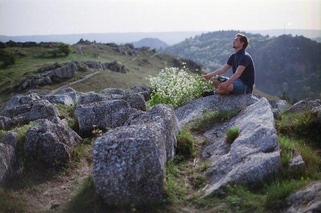 man sitting, meditating on a rock