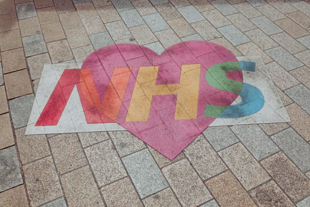 NHS with heart behind it on a pavement.
